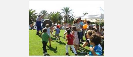 Grupo de niños jugando sobre un amplio cesped convarias pelotas.
